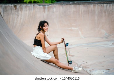 Portrait of a young, sporty and attractive Chinese Asian skater girl sitting down and taking a break with her skateboard in the skate park. She is smiling as she chills out.