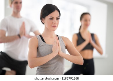 Portrait of young sporty attractive woman practicing yoga with group, doing meditation exercise vrikshasana pose with namaste, working out, indoor close up, yoga studio. Well-being concept