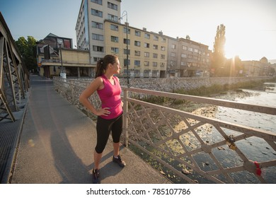 portrait of a young sporty jogging woman at sunny morning in the city