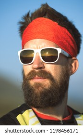Portrait of young sporty mountaineer man with beard.
