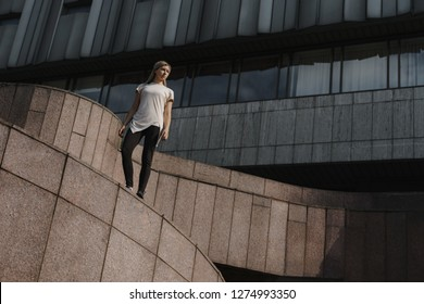 Portrait of young sporty parkour woman. Freeruning female athlete standing on roof.