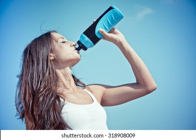 portrait of young sporty woman drinking isotonic drink, color effect
