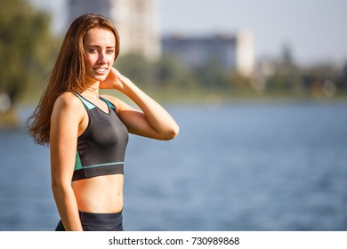 Portrait of young sporty woman resting after jogging in park near lake. Portrait of athletic girl in black top after fitness workout. Healthy lifestyle image with copyspace
