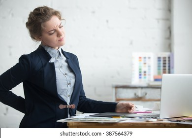 Portrait of young stressed woman sitting at home office desk in front of laptop, touching aching back with pained expression, suffering from backache after working on pc