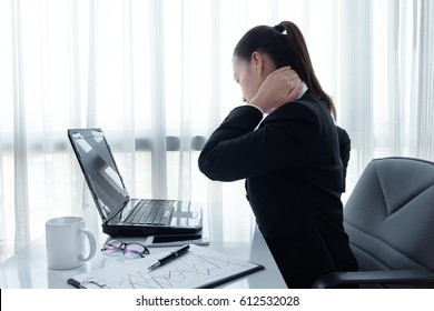 Portrait of young stressed woman sitting at office desk in front of laptop, touching aching back with pained expression, suffering from backache after working