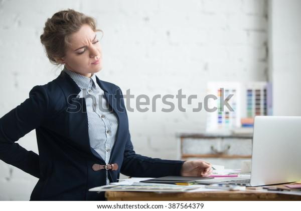 Портрет молодой стрессовой женщины, сидящей за домашним офисным столом перед ноутбуком, касаясь боли в спине с больным выражением, страдающей от боли в спине после работы на ПК