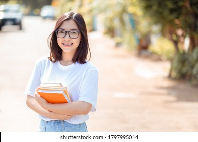 Portrait of young student asian woman wearing braces beauty smile with white teeth increase confidence holding book and wear glasses education study concept, Outdoor nature background copy space.