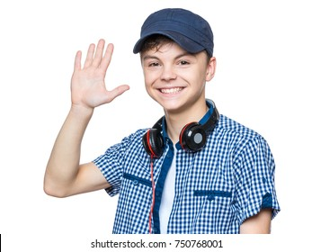 Portrait of young student with cap and headphones, isolated on white background. Confident teen boy waving a greeting. Studio shot of teenager saluting.