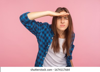 Portrait of young student girl in checkered shirt holding palm over her eyes, looking into distance with attentive view, watching horizon, far future. indoor studio shot isolated on pink background