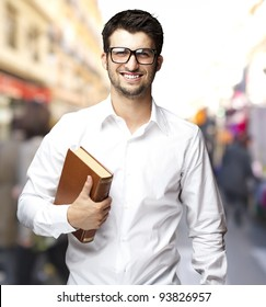 portrait of a young student holding a book against a street background