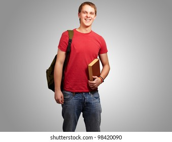 portrait of a young student holding a book and carrying a backpack over a grey background