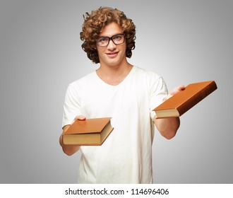 Portrait Of A Young Student Holding Books On Gray Background