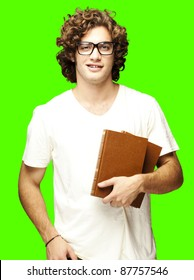 portrait of young student holding books over a removable chroma key background