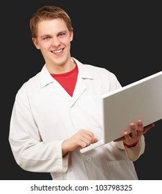 portrait of a young student holding a laptop over a black background