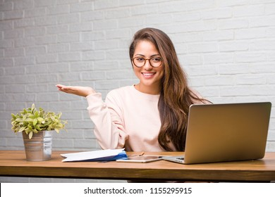 Portrait of young student latin woman sitting on her desk holding something with hands, showing a product, smiling and cheerful, offering an imaginary object