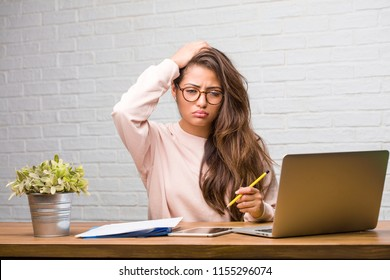 Portrait of young student latin woman sitting on her desk worried and overwhelmed, forgetful, realize something, expression of shock at having made a mistake