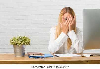 Portrait of young student sitting on her desk doing tasks feels worried and scared, looking and covering face, concept of fear and anxiety