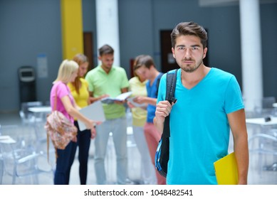 Portrait of a young student standing outside with friends in the background