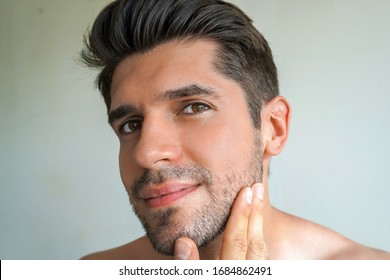 Portrait of a young stunning man with a perfect skin which is holding his clean beard