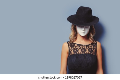 Portrait of a young style girl in black dress and white mask on gray background