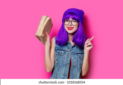 Portrait of young style hipster girl with purple hair and books on pink background