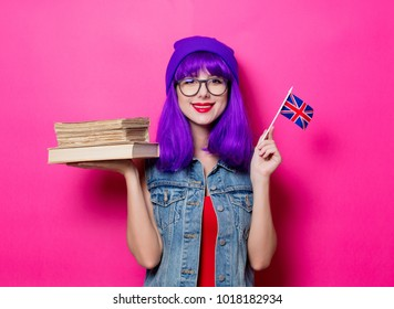 Portrait of young style hipster girl with purple hair and Great Britain flag in hand and books on pink background