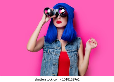 Portrait of young style hipster girl with blue hair and binoculars on pink background