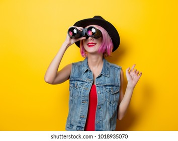 Portrait of young style hipster girl with pink hair style with binoculars on yellow background