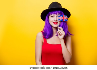 Portrait of young style hipster girl with purple hairstyle and Great Britain flag in hand on yellow background