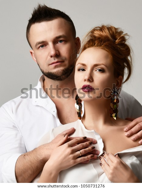 Portrait of young stylish couple in official clothes standing against gray background
