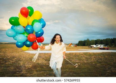 Portrait of young stylish girl with balloons using monopad