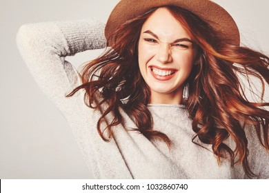 Portrait of young stylish laughing girl model in gray casual summer clothes in brown hat with natural makeup and long blowing hair isolated on gray background. Looking at camera