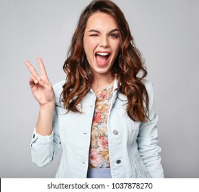 Portrait of young stylish laughing girl model in colorful casual summer clothes with natural makeup isolated on gray background. Looking at camera and showing peace sign
