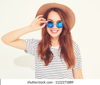 Portrait of young stylish laughing girl model in casual summer clothes in brown hat isolated on white background