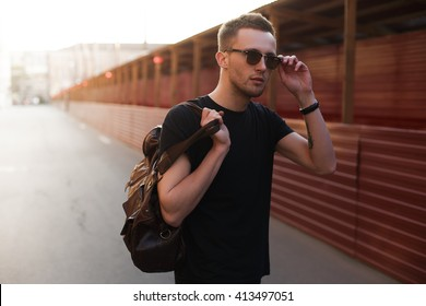 Portrait of young stylish man with bag in the street, life style.
