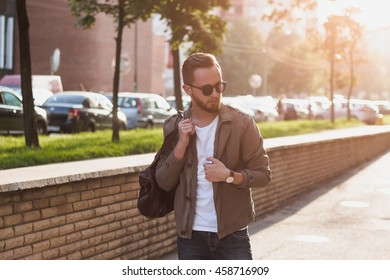 Portrait of young stylish man with bag in the street, life style