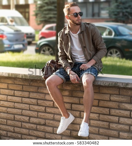 Portrait of young stylish man with bag in the street, lifestyle.