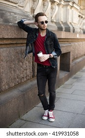 Portrait of young stylish man with coffee in the street. Lifestyle