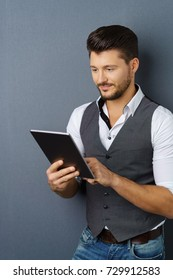 Portrait of young stylish man holding digital tablet against dark background