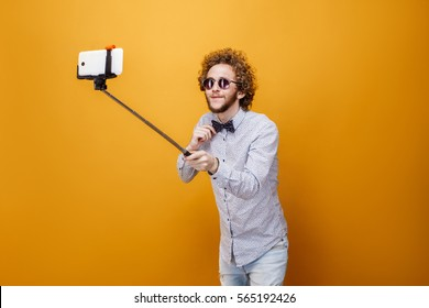 Portrait of young stylish man using monopad against of yellow background.Isolate.