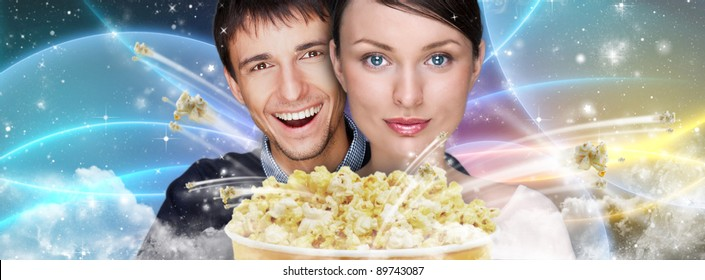 Portrait of young stylish modern couple watching movie against futuristic background embracing and eating exploding popcorn.