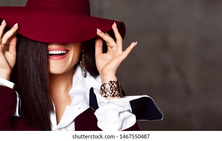 Portrait of young stylish noble woman brunette in black jacket and white shirt pulling down hat brim hiding her eyes and laughs on grey background