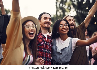 Portrait of young stylish people standing close to each other and raising hands. They looking away with happy smiles