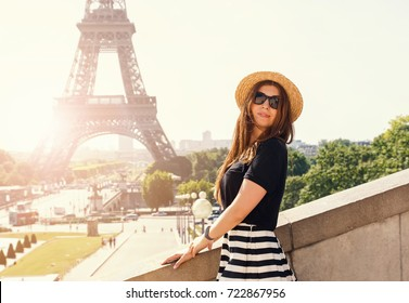 Portrait of young stylish woman in hat near the Eiffel tower in Paris on sunny day