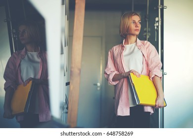 Portrait of young stylish woman holding bright yellow book standing near shelf in home interior, creative female designer with big magazine catalog standing in her studio while focused looking away