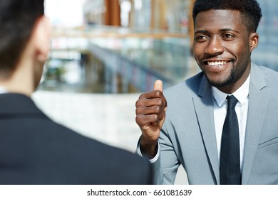 Portrait of young successful African-American businessman smiling and showing thumbs up while talking to partner, celebrating deal modern office building