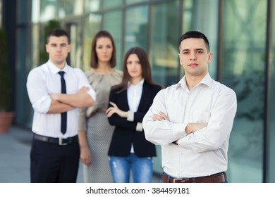 Portrait of young and successful business people. Focus on confident young businessman standing in front of his business team.