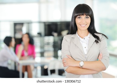 Portrait of a young successful business woman with working team at office