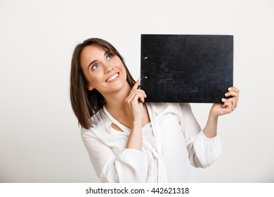 Portrait of young successful business woman smiling, holding folder over white background. Copy space.