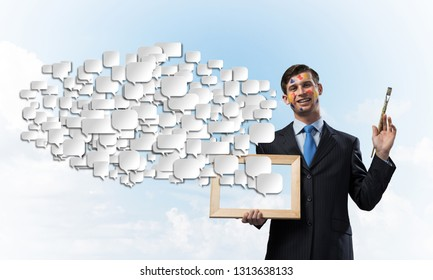 Portrait of young and successful businessman in black suit holding picture frame and paintbrush in hands while standing against blue cloudy skyscape view on background